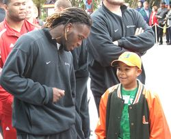 Running back Graig Cooper spends a moment with a young Canes fan.