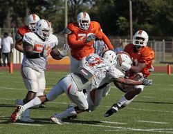 QB AJ Highsmith gets tackled by safety Vaughn Teleamaque (No. 7) and defensive end Adewale Ojomo